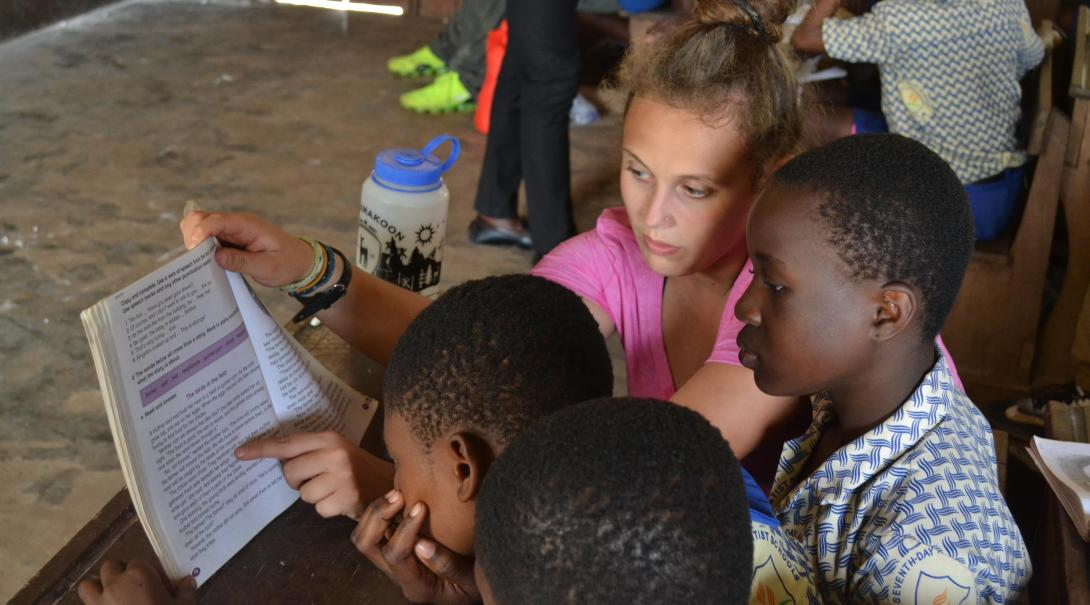 A Projects Abroad volunteer explains a text to some students in Ghana during her teaching English internship.